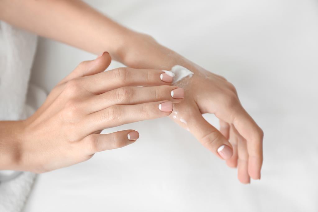 pessoa hidratando sua mão com creme