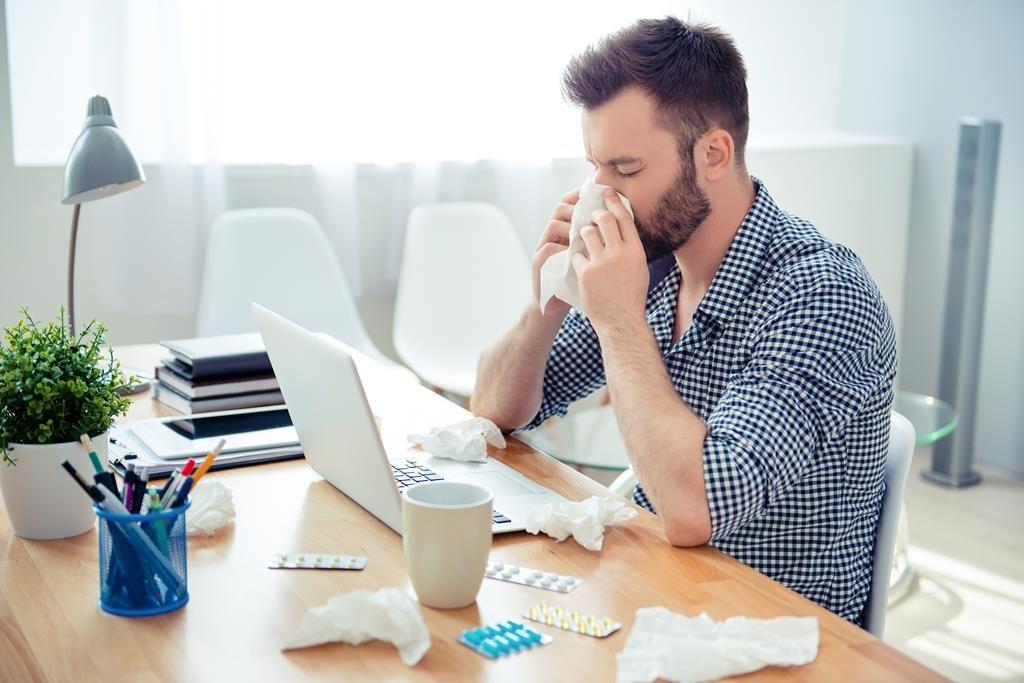 Homem limpando o nariz em frente ao computador