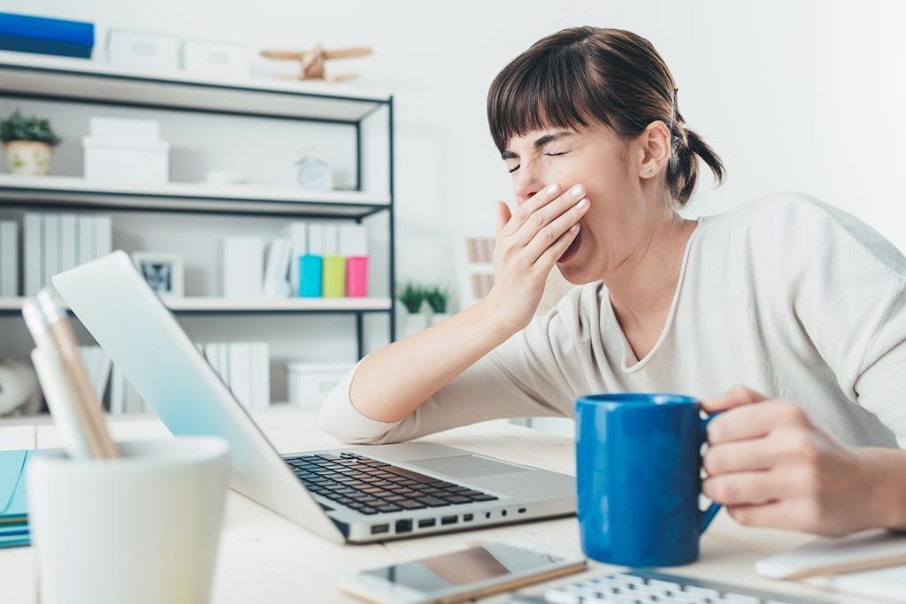 Mulher bocejando em frente ao computador
