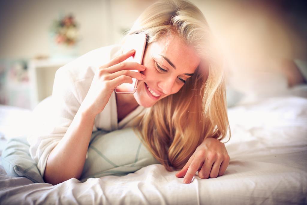 mulher feliz falando no celular