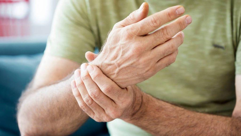 Pessoa pressionando o punho demonstrando aparente desconforto e dor na articulação.