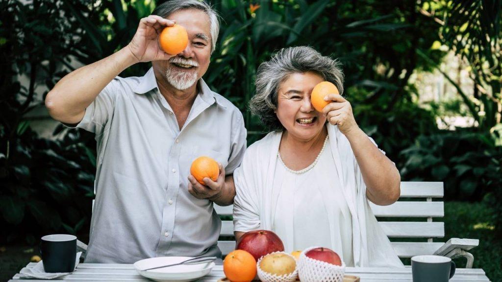 Homem e e mulher de meia idade, segurando frutas em frente aos seus rostos. Sentados atrás de uma mesa com frutas, pratos e canecas, demonstrando uma alimentação balanceada para prevenção dos problemas articulares.
