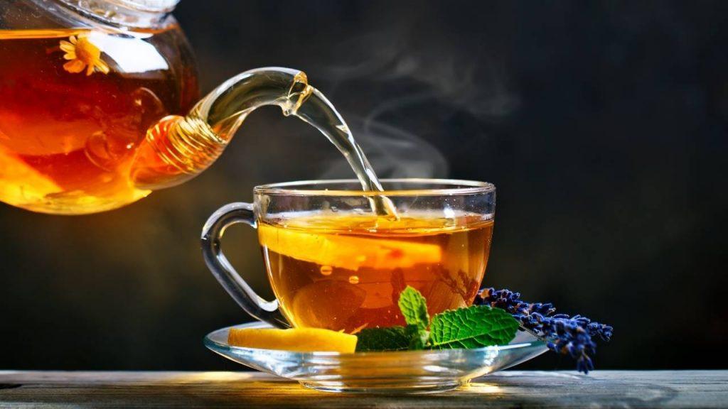 Xícara transparente, disposta sob mesa, sendo servida de chá, agente eficaz contra a retenção de líquido..