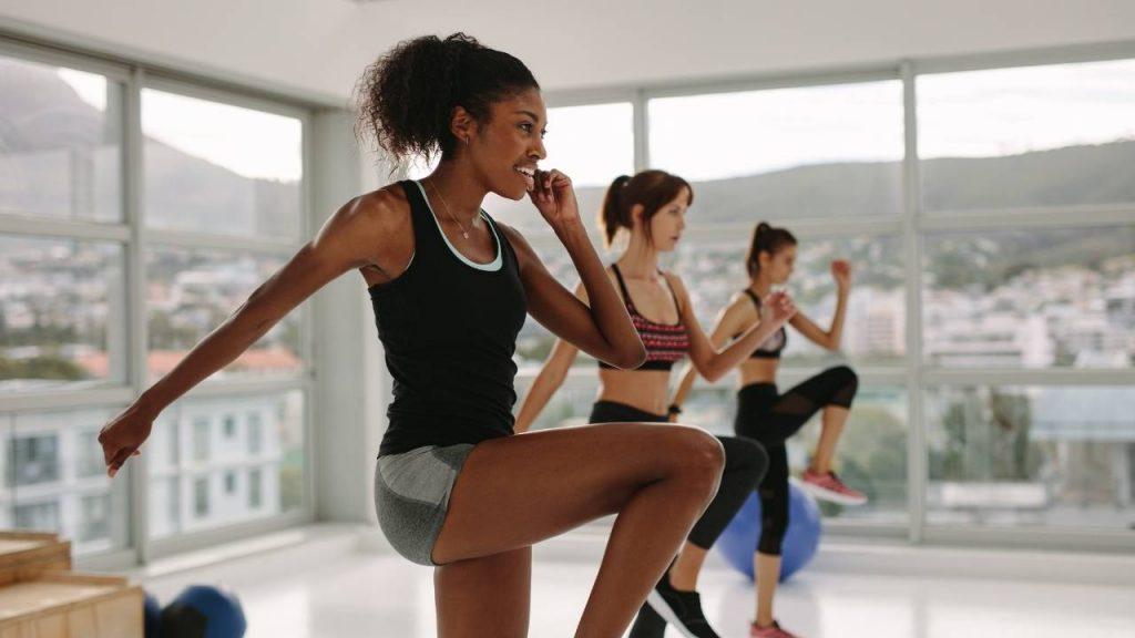 Três mulheres praticando exercícios físicos, prática ajuda a eliminar a água retina no corpo.