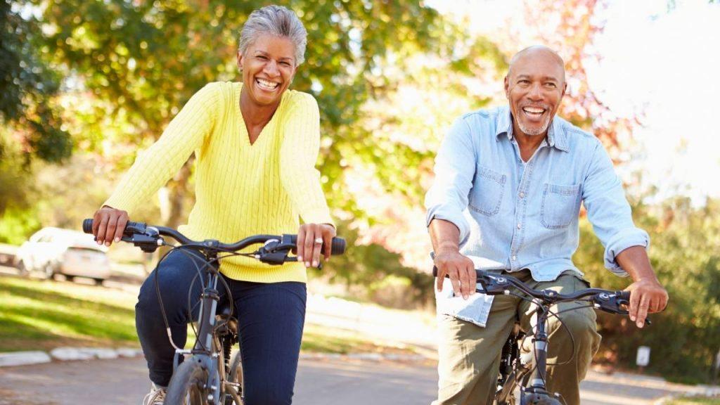 Mulher e homem, de meia idade, andando de bicicleta em parque, demonstrando hábitos saudáveis que evitam dor nas articulações.