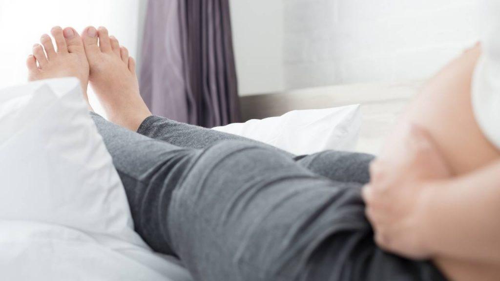 Mulher gestante, com os pés sob travesseiros, para aliviar os inchaços causados pela retenção de líquido.