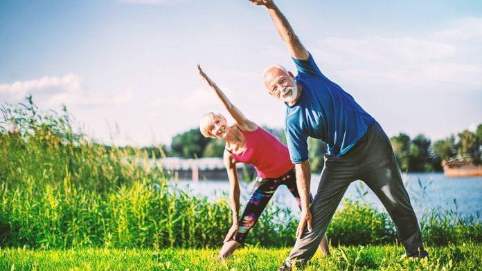 Homem e mulher, idosos, se exercitando em um parque, demonstrando uma bons hábitos e boa condição física.