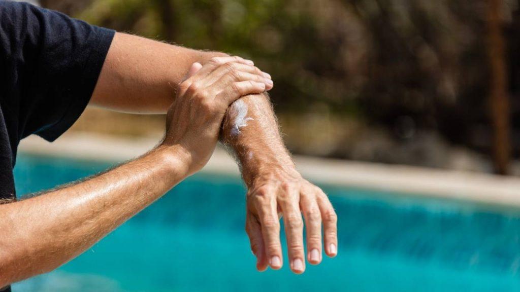 Pessoa exposta ao sol, aplicando protetor solar nos braços como forma de proteção da pele.
