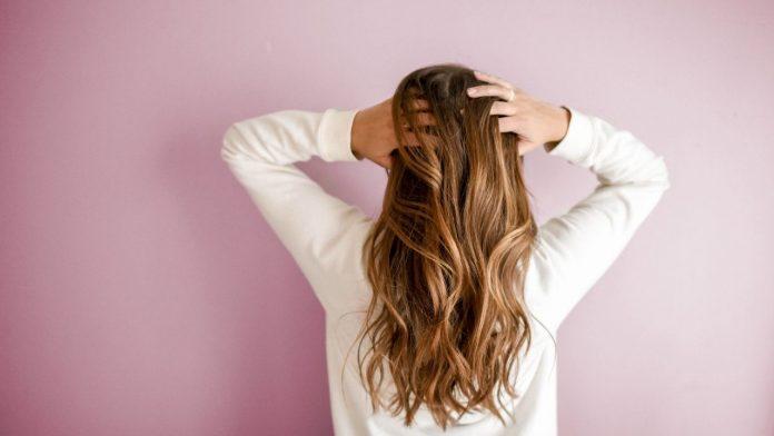 Mulher de costas, comas duas mãos nos cabelos.