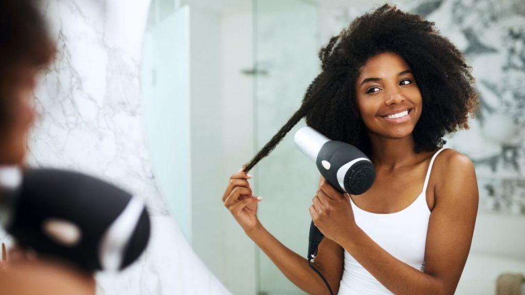 Uma mulher em frente ao espelho, segurando uma mecha com a uma das mãos e com a outra o secador de cabelos.