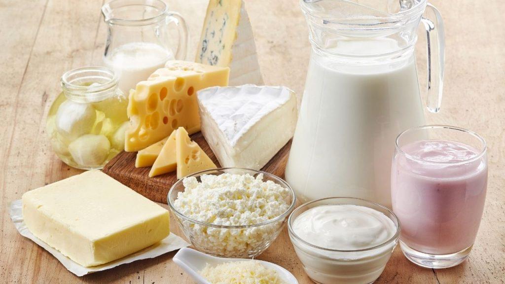 Na imagem, sob uma mesa, estão dispostos diversos tipos de queijos, iogurtes, manteigas e leite, como opção de alimentação rica e nutriente e vitamina para cabelos.